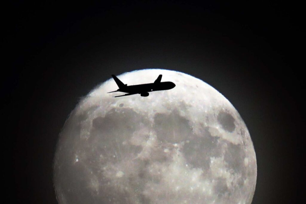 A commerical jet flies in front of the moon on its approach to Heathrow airport in west London on November 13, 2016. Tomorrow, the moon will orbit closer to the earth than at any time since 1948, named a 'supermoon', it is defined by a Full or New moon coinciding with the moon's closest approach to the Earth. / AFP / Adrian DENNIS (Photo credit should read ADRIAN DENNIS/AFP/Getty Images)