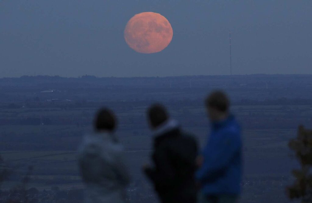 "A family watch the moon rise a day before the ""supermoon"" spectacle on Beacon Hill near Loughborough, Britain, November 13, 2016. REUTERS/Darren Staples"