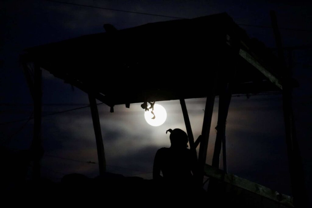 "A woman sits on the rooftop terrace of a house during the ""supermoon"" in Port-au-Prince, Haiti, November 13, 2016. REUTERS/Andres Martinez Casares"