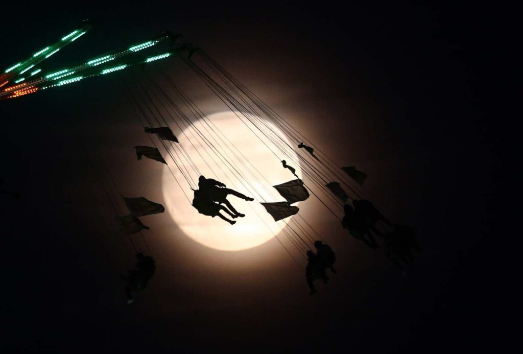 "People on a funfair ride are silhouetted against the moon a day before the ""supermoon"" spectacle, in London, Britain November 13, 2016. REUTERS/Neil Hall"