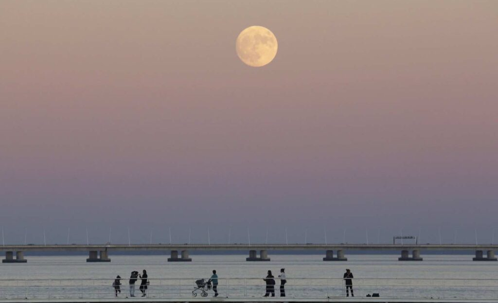 People stroll along the Tagus riverside in Lisbon as the moon rises Sunday, Nov. 13 2016. The so-called Supermoon on Nov. 14, 2016, will be the closest a full moon will have been to Earth since 1948. (AP Photo/Armando Franca)