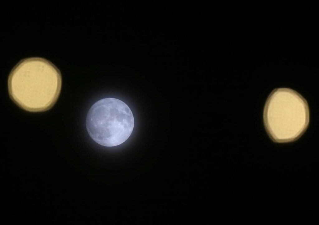 """Streetlights are seen next to the moon a day before the """"supermoon"""" spectacle, in London, Britain November 13, 2016. REUTERS/Neil Hall"""