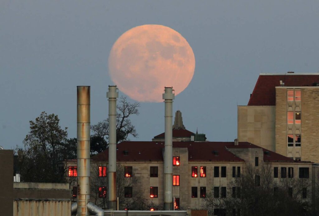 The moon rises beyond the University of Kansas campus in Lawrence, Kan., Sunday, Nov. 13, 2016. The morning's supermoon will be the closest a full moon has been to Earth since Jan. 26, 1948. (AP Photo/Orlin Wagner)